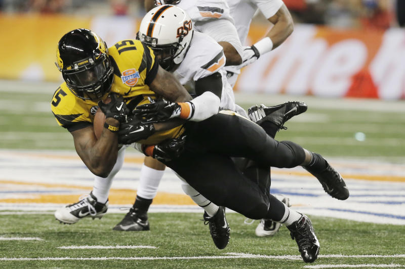 Missouri wide receiver Dorial Green-Beckham (15) is tackled by Oklahoma State safety Daytawion Lowe (8) during the second half of the Cotton Bowl NCAA college football game on Friday, Jan. 3, 2014, in Arlington, Texas