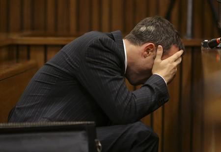 Olympic and Paralympic track star Oscar Pistorius reacts as he reaches for a bucket in the dock during his trial for the murder of his girlfriend Reeva Steenkamp, at the North Gauteng High Court in Pretoria, March 10, 2014. REUTERS/Siphiwe Sibeko