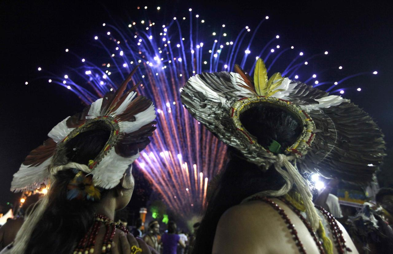 Brazilian indigenous people watch fireworks exploding in the sky during the closing ceremony of the XII Games of the Indigenous People in Cuiaba November 16, 2013. REUTERS/Paulo Whitaker (BRAZIL - Tags: SPORT SOCIETY TPX IMAGES OF THE DAY)