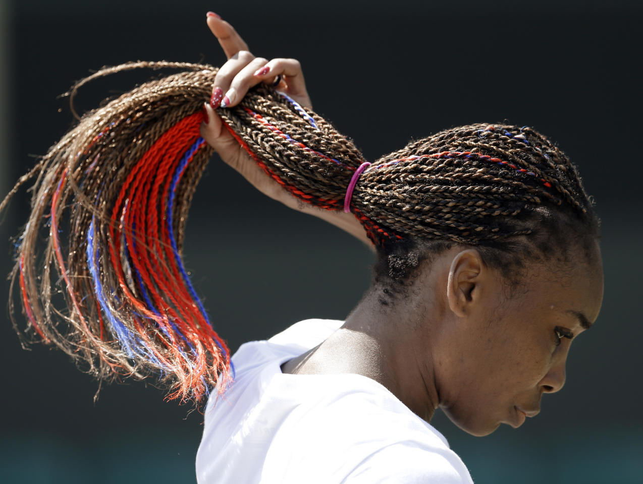 Venus Williams, of the United States, adjusts her hair, which contains red and blue strands, during practice at the All England Lawn Tennis Club at Wimbledon, in London, at the 2012 Summer Olympics, Thursday, July 26, 2012. Tennis competition is scheduled to begin Saturday, July 28. (AP Photo/Mark Humphrey)
