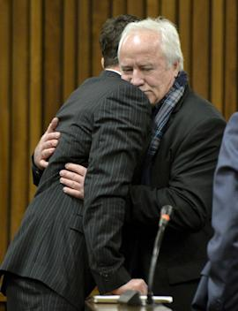 Oscar Pistorius, left, gets a hug from his estranged father, Henk Pistorius, right, in court Friday. (AP)