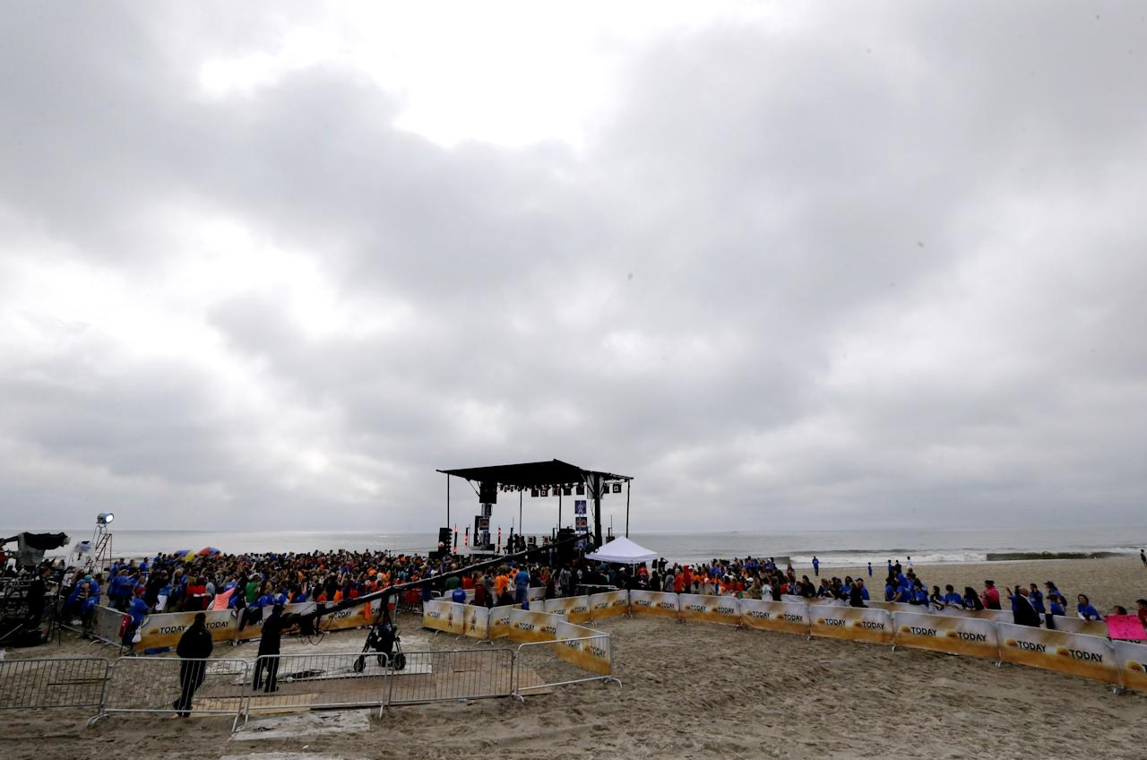 People gather around a stage as musical group Fun performs on the beach, Friday, May 24, 2013, in Seaside Heights, N.J. New Jersey Gov. Chris Christie cut a ribbon to symbolically reopen the state's shore for the summer season, seven months after being devastated by Superstorm Sandy. Several beach communities have annual beach ribbon cuttings, announcing they are back in business. But this year's ceremonies are more poignant seven months after a storm that did an estimated $37 billion of damage in the state. (AP Photo/Julio Cortez)