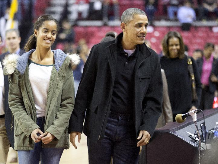 President Barack Obama, center, with first lady Michelle Obama, back right, and their daughters Malia, left, and Sasha, arrive at the Comcast Center in College Park, Md., to watch his brother-in-law Oregon State Beavers Coach Craig Robinson's basketball team play against the Maryland Terrapins, Sunday, Nov. 17, 2013. (AP Photo/Manuel Balce Ceneta)