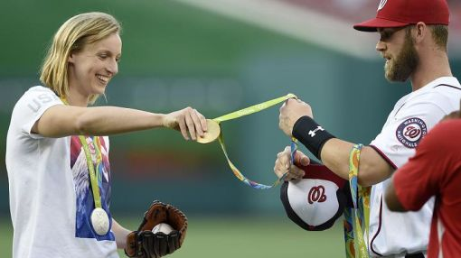 Gentleman Bryce Harper assists Katie Ledecky with Olympic medals