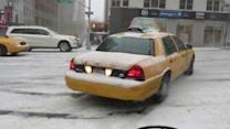 Taxi Sliding in a Thin Coat of Snow on Street of New York