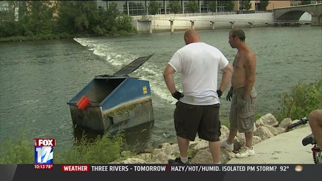 Two Men Use Buckets To Remove Dumpster From River