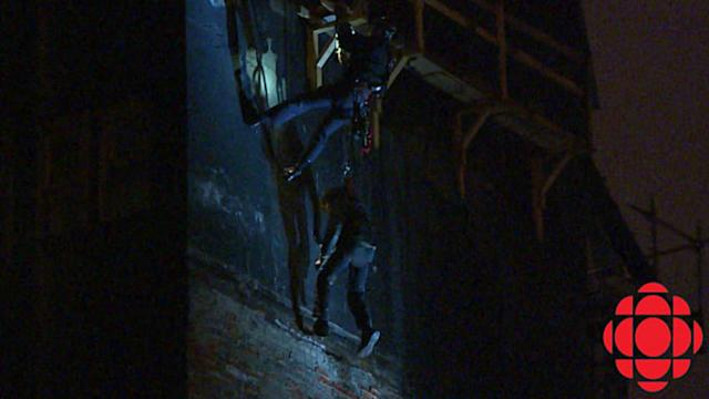 RAW: Man dangling from building rescued